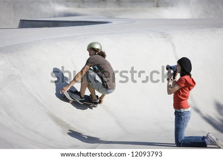 Boy dies tricks at the skateboard park as girl videotapes - stock photo
