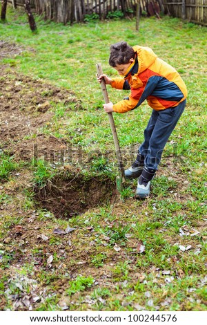 Boy digging on a grass field in the countryside - stock photo