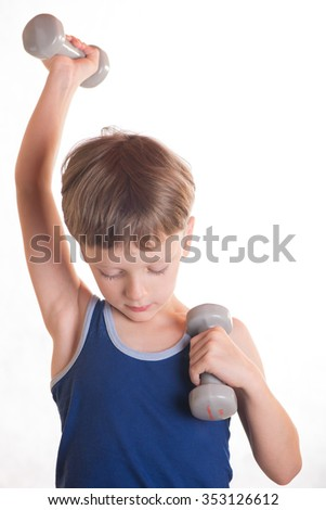 Boy does physical exercises with dumbbells bending and extending arms alternately