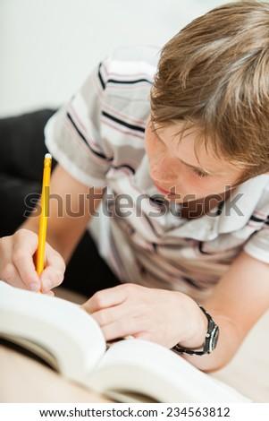 Boy doing his homework on floor - stock photo