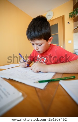 boy doing school homework from mathematics in workbook