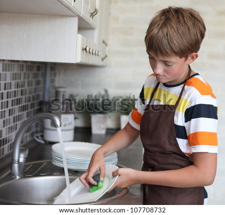 boy doing the dishes - stock photo