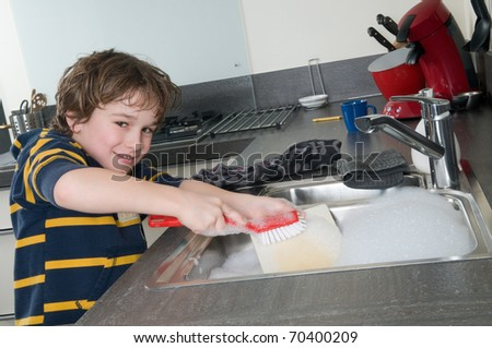 Boy doing the dishes in a modern kitchen