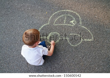 Boy drawing car with chalk - stock photo