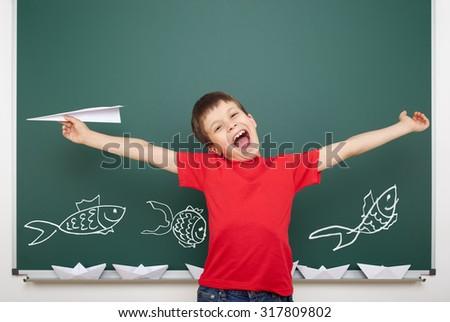 boy drawing fish on school board - stock photo