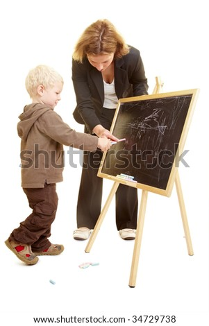 Boy drawing on a blackboard and teacher helping - stock photo