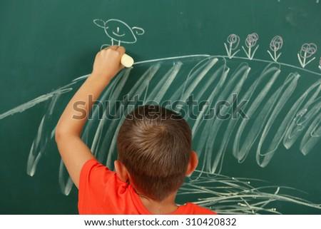 Boy drawing on blackboard, close-up - stock photo
