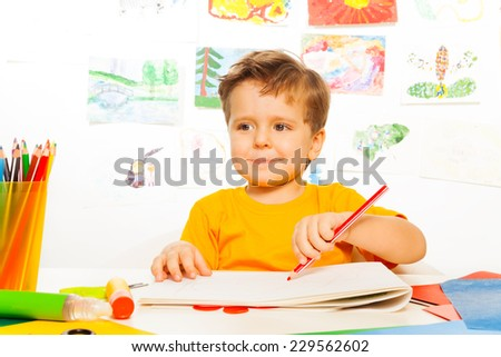 Boy drawing with pencil on the paper at table - stock photo