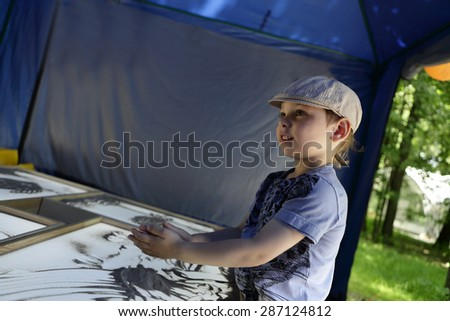 Boy draws with sand on the workshop - stock photo