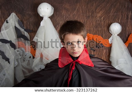 Boy dressed like vampire for Halloween party. Brown background and white ghosts - stock photo