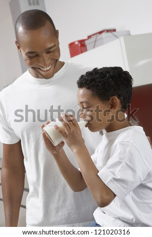 Boy drinking glass of milk in front of father at home
