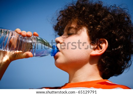 Boy drinking water against blue sky