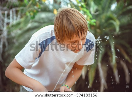 boy drinking water from a fountain - stock photo