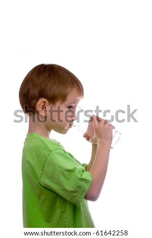 boy drinks water from a glass on a white background - stock photo