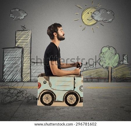 Boy driving cardboard car in drawing city - stock photo