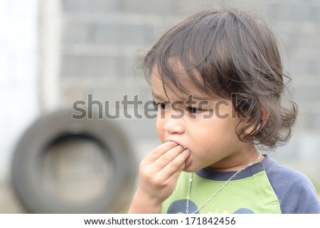 boy eating a cookie in the park - stock photo