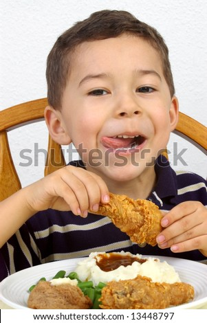 Boy eating a fried chicken dinner - stock photo