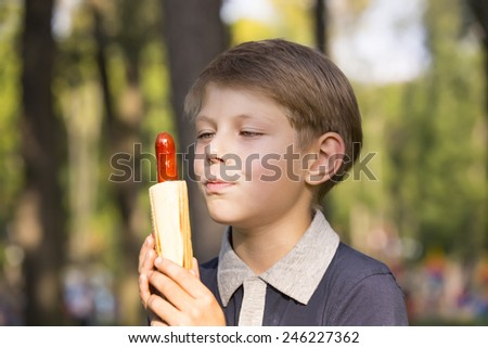 boy eating a hot dog on the street - stock photo