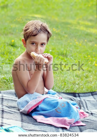 Boy eating a sandwich at a picnic. - stock photo