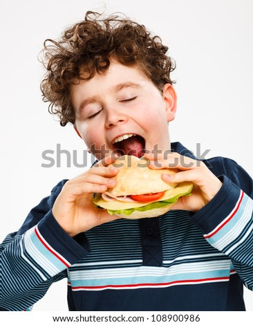 Boy eating big sandwich - stock photo
