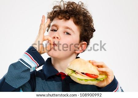 Boy eating big sandwich showing OK sign - stock photo