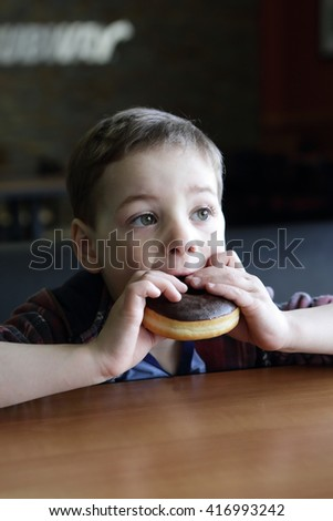 Boy eating donuts with chocolate frosting in cafe - stock photo