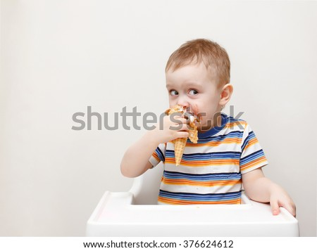 boy eating ice cream sitting in a high chair. cute child enjoying an ice cream in a waffle cone. looks toward. copy space for your text - stock photo