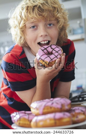 Boy Eating Iced Donut In Kitchen - stock photo