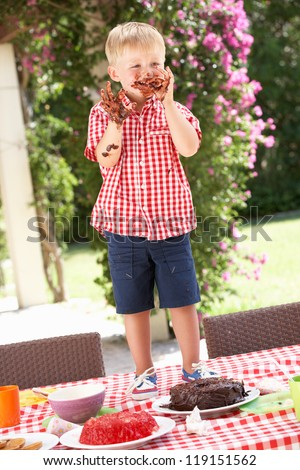 Boy Eating Jelly And Cake At Outdoor Tea Party - stock photo