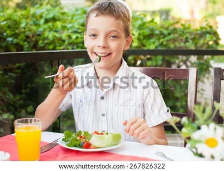 Boy eating salad at a cafe. Teenager eating outdoors - stock photo