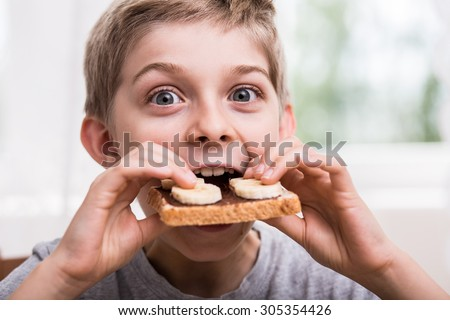 Boy eating toast with chocolate and banana - stock photo