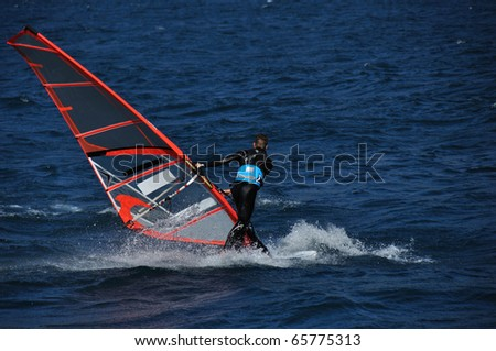 Boy engaged in acrobatics with his windsurfing