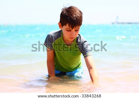 Boy enjoying on beach - stock photo