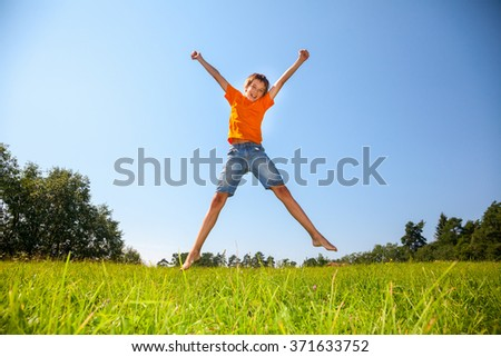 Boy enjoying summertime jumping on the sunny meadow in a summer forest - stock photo