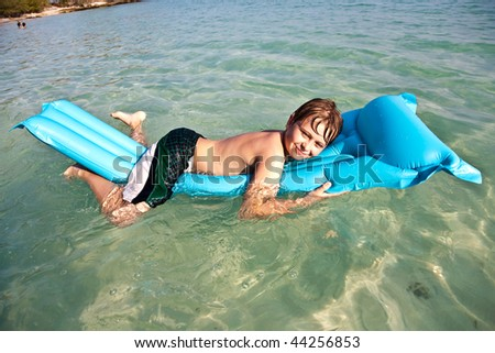 boy enjoys lying on the air mattress at the crystal clear water at a beautiful fine sandy beach