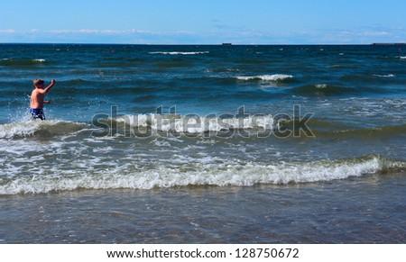 Boy enjoys the waves of the beautiful sea - stock photo