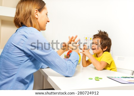 Boy exercises putting fingers with therapist - stock photo