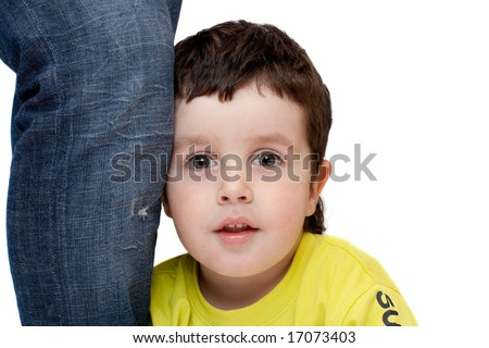 Boy, expressing astonishment, leaned on his mother leg, isolated