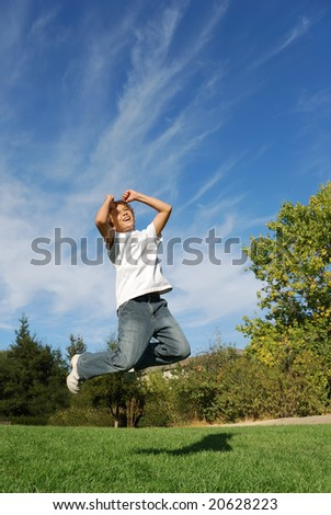 Boy expressing happiness by jumping in the park - stock photo