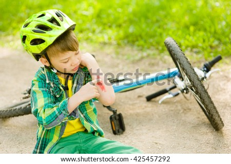 boy fell from the bike in a park - stock photo