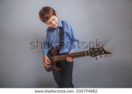 boy fingered guitar strings - stock photo