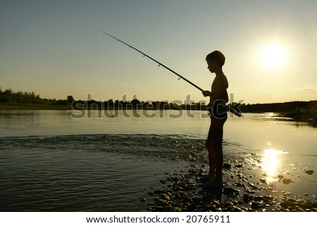 Boy fishes on the bank of small river