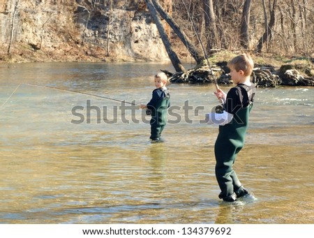 Boy fishing a trout on a fly rod while his brother/friend looks on (focus on boy in front) - stock photo