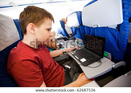 boy flies in the plane and plays the laptop - stock photo