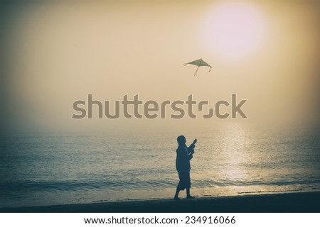 Boy flying a kite on beach at sunrise - stock photo