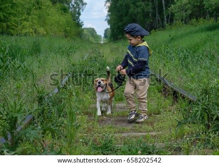 Boy, four years old walks on a leash with a Beagle dog on the railway