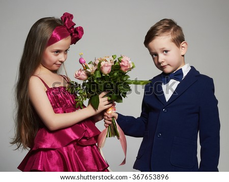 boy gives a girl flowers.little beautiful couple.kids love,valentine.roses bouquet - stock photo
