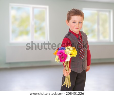 boy gives flowers.kindergarten, the concept of childhood and joy, teens - stock photo