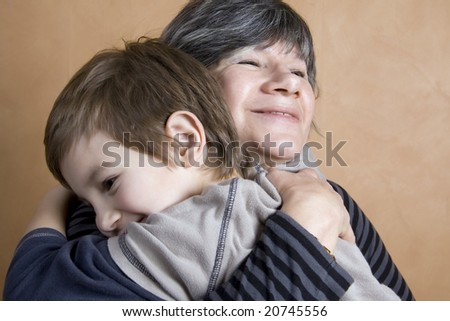 Boy giving his grandmother a huge hug - stock photo
