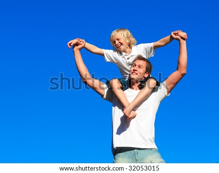 Boy giving kid a piggyback ride against the blue sky - stock photo